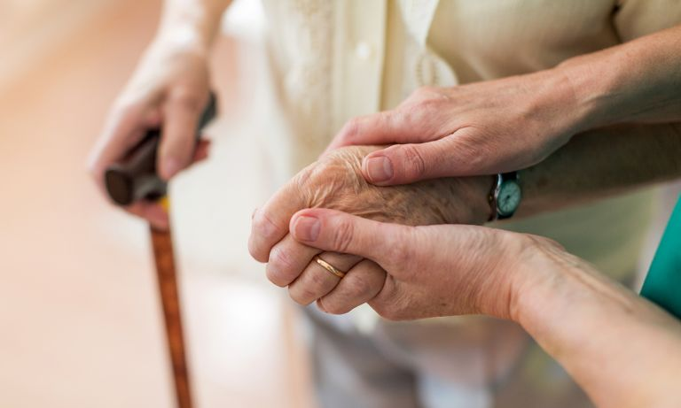 womans hands supporting elder by arm 768